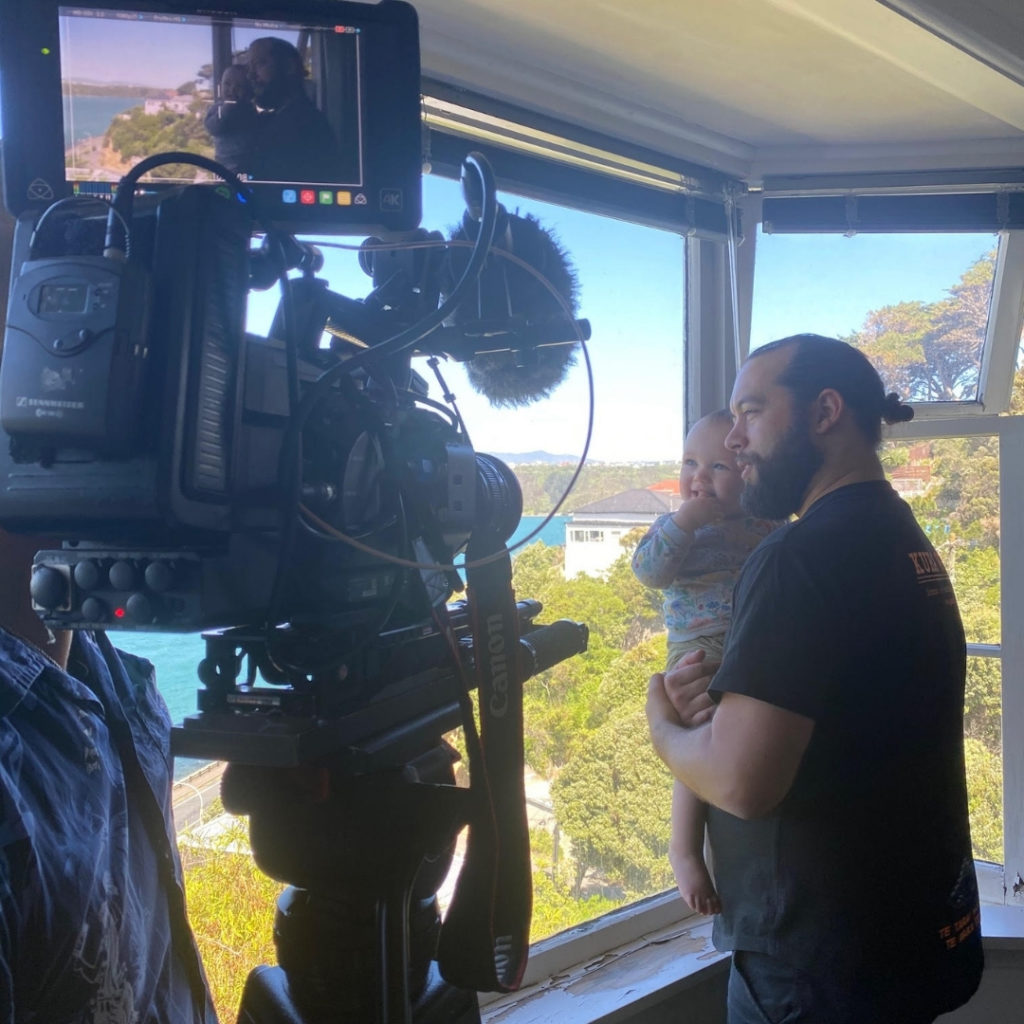 Te Kawa Robb and his pēpi looking out the window while being filme.
